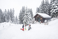 Austria, Altenmarkt-Zauchensee, family with sledges at wooden house at Christmas time - HHF05488