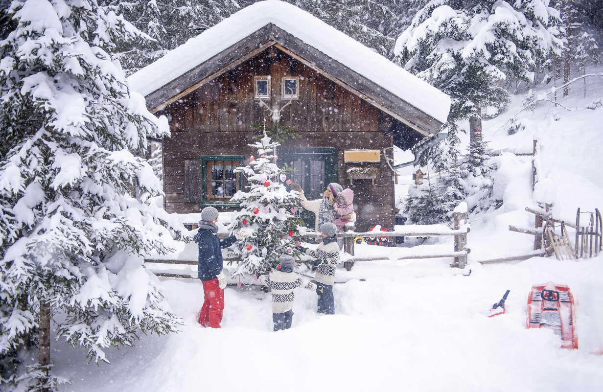 Austria, Altenmarkt-Zauchensee, family decorating Christmas tree at wooden house - HHF05494 - Hans Huber/Westend61