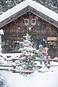 Austria, Altenmarkt-Zauchensee, mother with little son decorating Christmas tree at wooden house - HHF05497