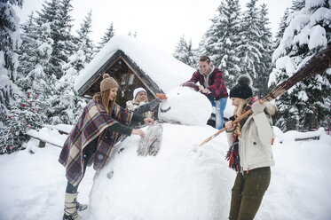 Austria, Altenmarkt-Zauchensee, friends building up big snowman at wooden house - HHF05498