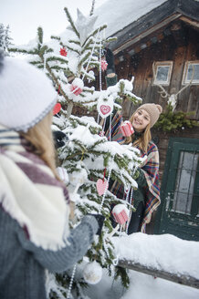 Austria, Altenmarkt-Zauchensee, two young women decorating Christmas tree at wooden house - HHF05501