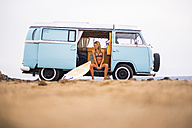 Young woman with surfboard sitting in van on the beach - SIPF01803