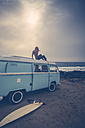 Young woman sitting on roof of a van on the beach - SIPF01809