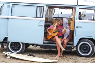 Young couple with guitar and surfboard in van on the beach - SIPF01812