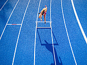 Top view of female runner crossing hurdle on tartan track - STSF01332