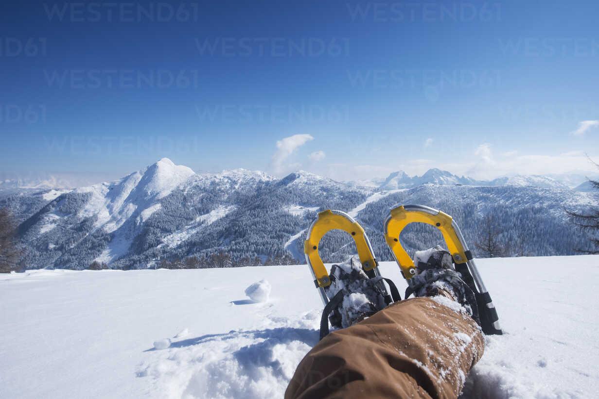 Austria, Salzburg State, Altenmarkt-Zauchensee, man with snowshoes lying in deep snow - HHF05507 - Hans Huber/Westend61