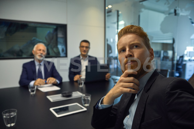 Portrait of businessman turning round in a meeting - ZEDF00913