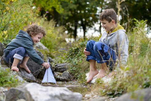 Two boys playing with a toy boat in a brook - LBF01693