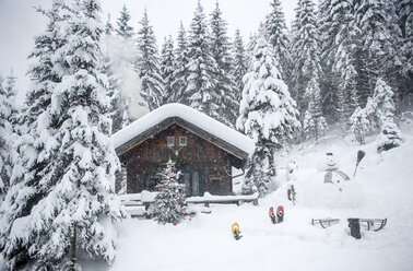 Austria, Altenmarkt-Zauchensee, snowman, sledges and Christmas tree at wooden house in snow - HHF05510