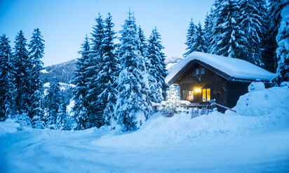 Austria, Altenmarkt-Zauchensee, sledges, snowman and Christmas tree at illuminated wooden house in snow at dusk - HHF05513