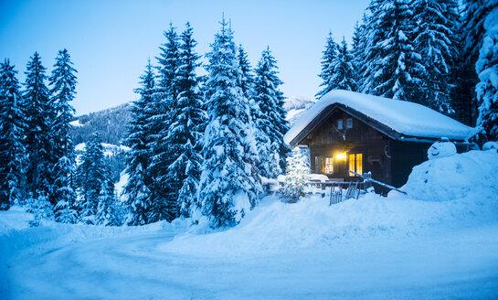 Austria, Altenmarkt-Zauchensee, sledges, snowman and Christmas tree at illuminated wooden house in snow at dusk - HHF05513