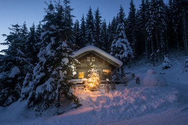 Austria, Altenmarkt-Zauchensee, sledges, snowman and Christmas tree at illuminated wooden house in snow at night - HHF05516