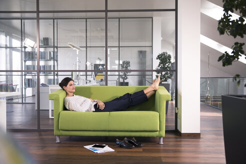 Businesswoman taking a nap lying on a couch in the office - FKF02606