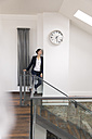 Businesswoman leaning against wall in office, waiting under clock - FKF02612