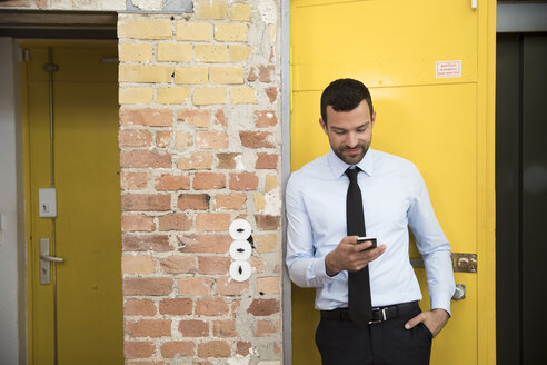 Businessman leaning in front of elevator using smartphone - FKF02627