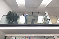 Successful businessman standing at railing in his office, using smartphone - FKF02654