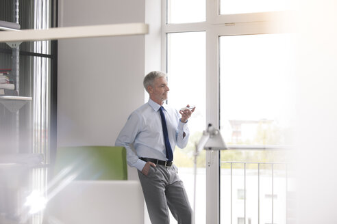 Mature businessman standing in office, using smartphone - FKF02669