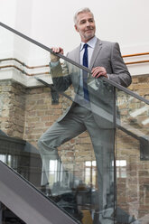 Mature businessman in modern office standing on stairs - FKF02717