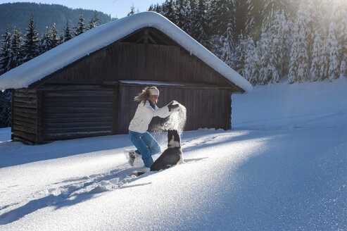 Austria, Altenmarkt-Zauchensee, happy young woman playing with dog in snow - HHF05517