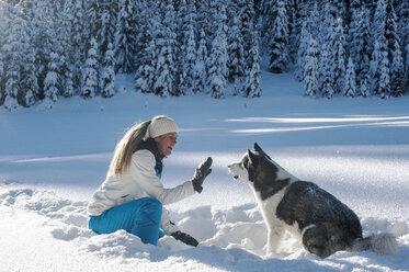 Austria, Altenmarkt-Zauchensee, young woman sitting with dog in snow - HHF05520