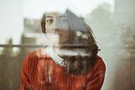 Portrait of serious young woman behind glass pane - FEXF00288