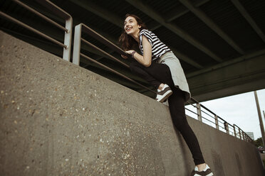 Happy young woman on railing under a bridge - FEXF00309