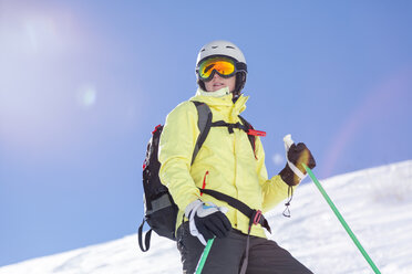 Austria, Bludenz, woman with ski helmet and avalanche backpack in the mountains - MMAF00166