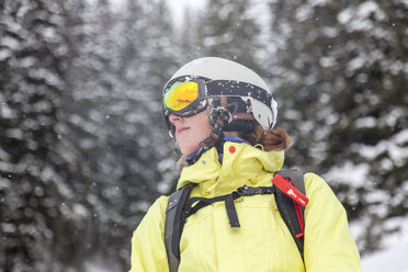 Austria, Kitzbuehel, woman with ski helmet and avalanche backpack in snow - MMAF00169