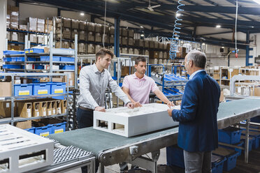 Business people standing on shop floor, discussing product improvement - DIGF02967