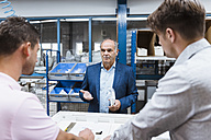 Business people standing on shop floor, discussing product improvement - DIGF02970