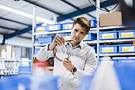 Businessman standing in shop floor, testing products - DIGF02973