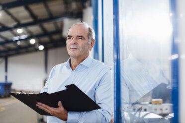 Senior businessman standing on shop floor, holding files - DIGF02982