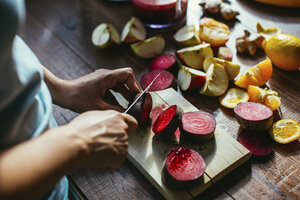 Woman's hands chopping beetroot for squeezing juice - MOMF00279