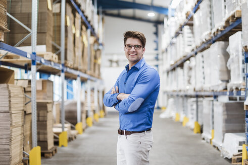 Businessman standing in warehouse, portrait - DIGF02999