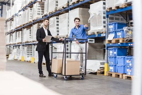 Businessmen in warehouse loading cardboard boxes on transport cart - DIGF03008