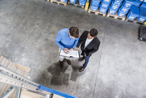 Two businessmen having a meeting in company warehouse - DIGF03011