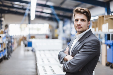 Young manager standing in shop floor, portrait - DIGF03038