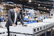 Young manager standing in shop floor reading papers - DIGF03041