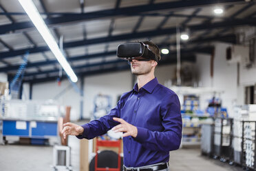 Company employee wearing VR goggles in shop floor - DIGF03044