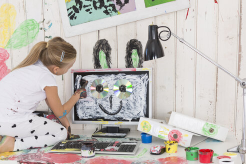 Girl painting rabbit ears on PC in office - DRF01728