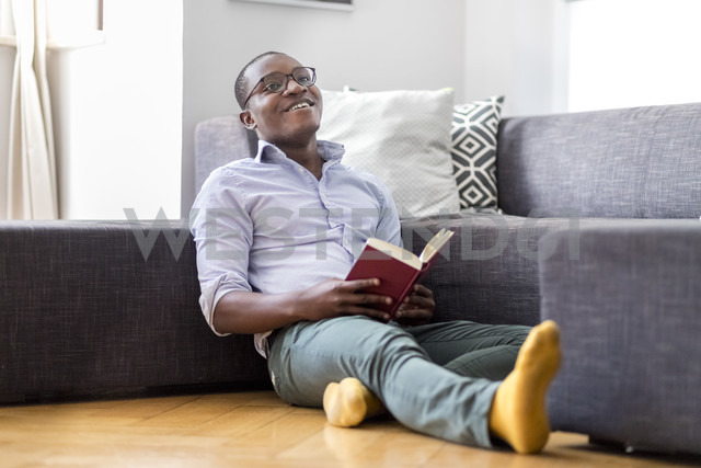 Happy young man sitting on the floor in the living room reading book - MMAF00178