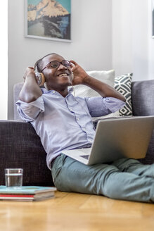Happy young man sitting on the floor in the living room using laptop and headphones - MMAF00181
