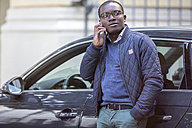 Portrait of young man on the phone leaning against car - MMAF00184