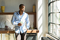 Young entrepreneur standing in company kitchen, drinking coffee - SPCF00206