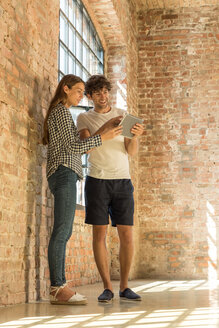 Two young entrepreneurs viewing loft for a start-up company, reading rental contract on digital tablet - SPCF00215