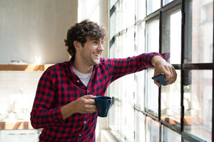 Young entrepreneur standing in company kitchen, drinking coffee - SPCF00224
