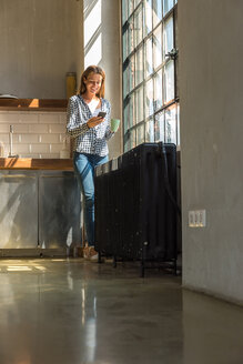 Young woman entrepreneur standing in company kitchen, drinking coffee, using smartphone - SPCF00227