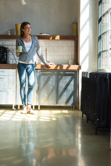 Young woman entrepreneur standing in company kitchen, drinking coffee - SPCF00230