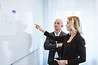 Businessman looking at businesswoman at whiteboard in office - DIGF03083