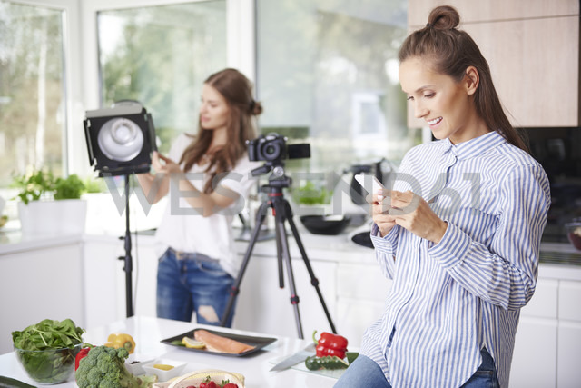 Woman using smartphone before cooking - ABIF00036